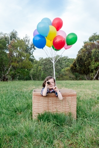 Young girl playing in a hot air balloon made from cardboard and balloons