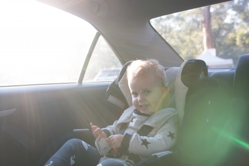 Young girl playing in her car seat in the afternoon sun