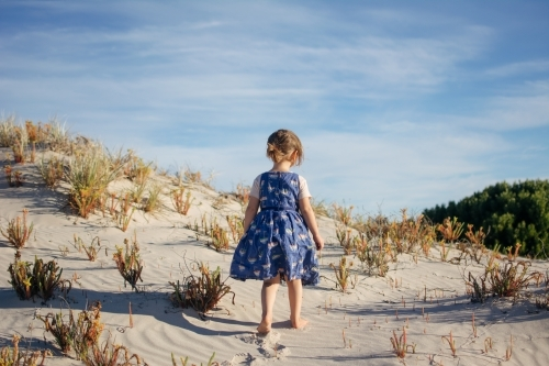 Young girl playing in sand dunes