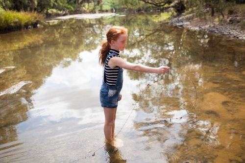 Young girl playing in the river