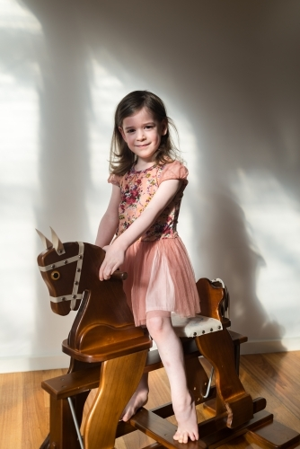 Young girl riding a wooden rocking horse