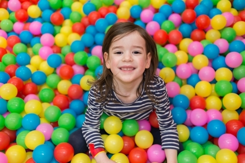 Young girl sitting in a playpen filled with colourful balls