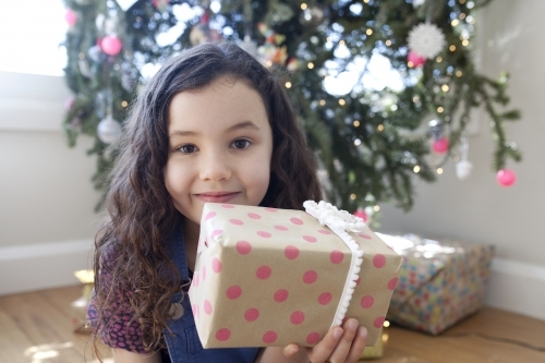 Young girl sitting in front of christmas tree holding a present up in front of her face