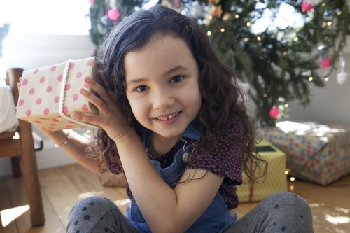 Young girl sitting in front of christmas tree holding a present up to her ear