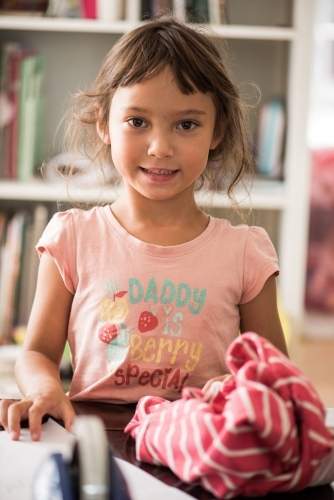 Young girl smiling at camera indoors.