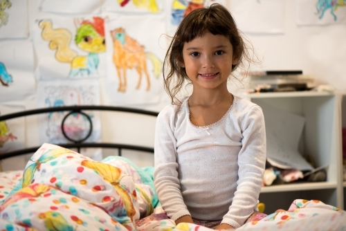 Young girl smiling at camera sitting on bed in bedroom