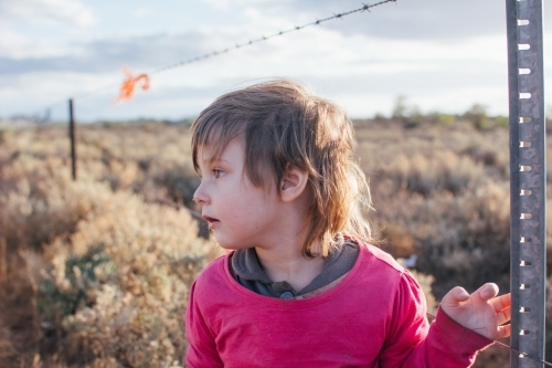 Young girl standing by barbwire fence