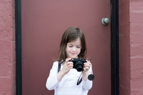 Young girl standing in front of a pink door looking at her camera