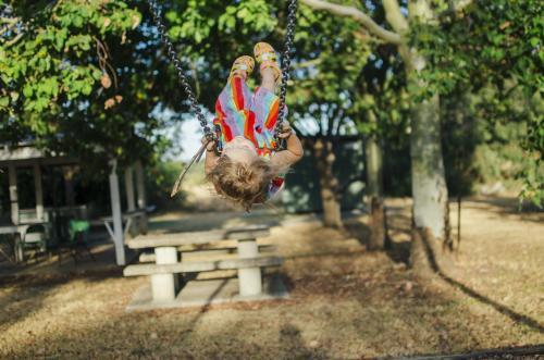 Young girl swinging high on swings at playground