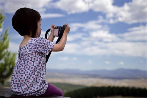 Young girl using a camera whilst on holiday to take a photo of a valley