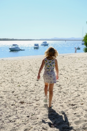 Young girl walking towards the beach