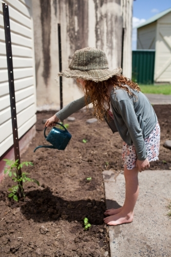 Young girl watering a garden