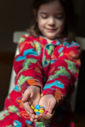 Young girl wearing dinosaur pyjamas holding out a handful of colourful smarties