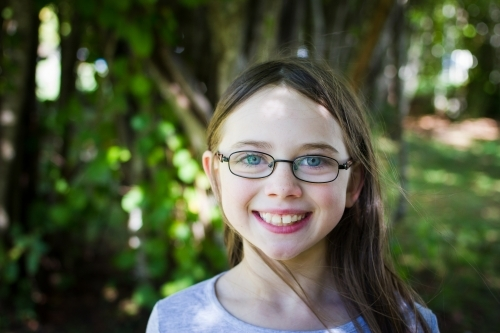 Young girl wearing glasses in dappled light