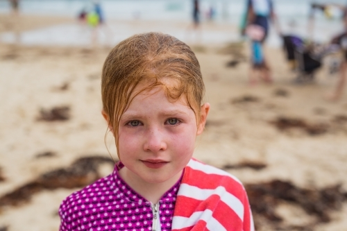 young girl with bloodshot eyes and messy hair after being dumped by a wave