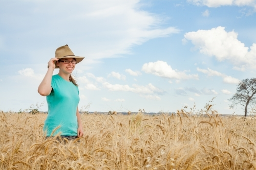 Young girl with hat on standing in paddock of bearded wheat crop on a farm