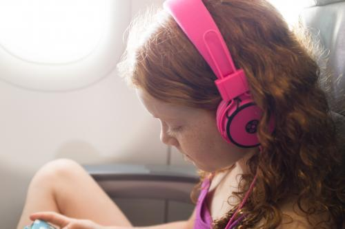 Young girl with headphones on a passenger plane