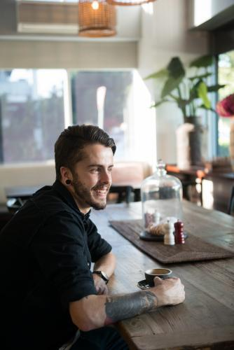 Young hipster man drinking coffee in a modern cafe