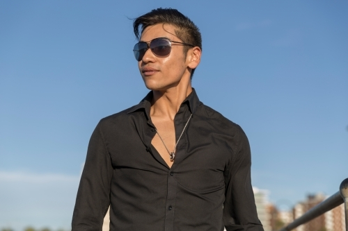 Young hispanic male in black shirt and sunglasses with blue sky backdrop