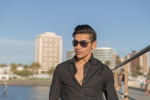 Young hispanic man wearing black shirt and sunglasses in trendy seaside setting