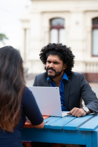 Young Indian businessman conducting meeting outdoors