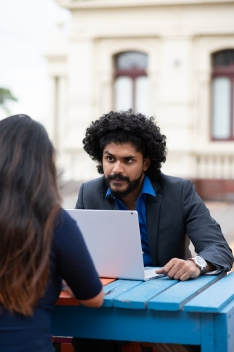 Young Indian businessman using laptop during outdoor meeting