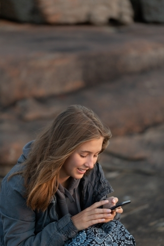Young lady sitting on rocks and looking at smartphone at dusk
