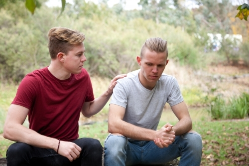 Young male same sex couple having a serious conversation in a rural setting