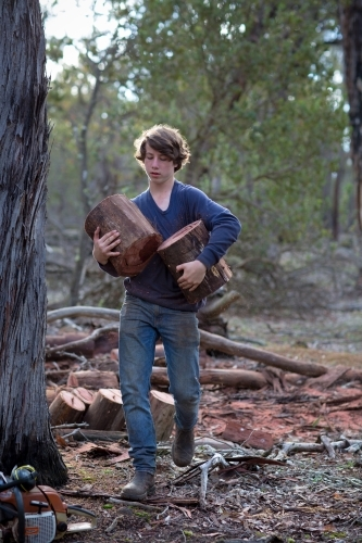 Young man carrying logs for firewood