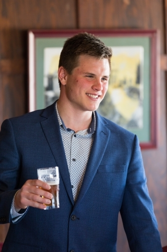 Young man in a suit smiling and holding a beer