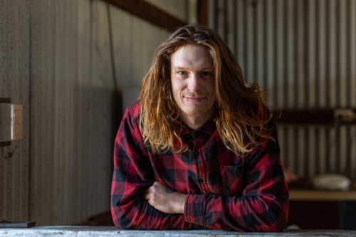 young man in flannel shirt leaning on bench in shed