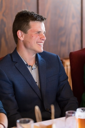 Young man in suit, sitting in restaurant, laughing