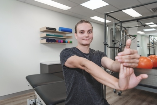 Young man stretching at physiotherapy clinic