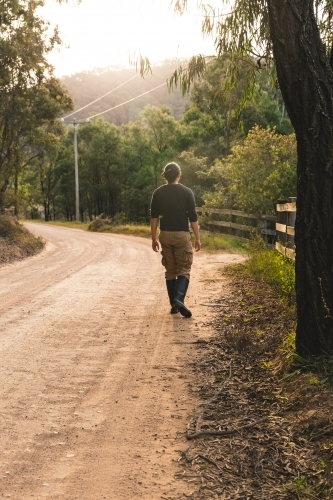 Young man walking down winding dirt road on bush walk at sunset outside rural property