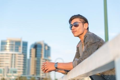 Young man watching the sunset with condos in the background
