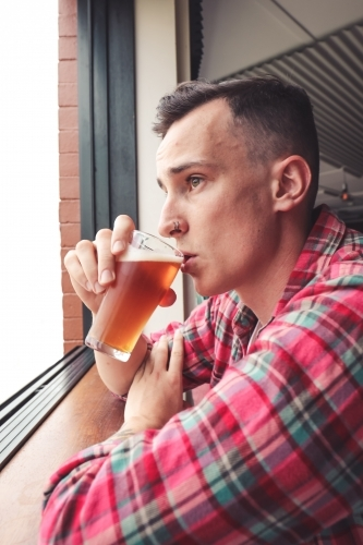 Young man wearing a flannel sipping a glass of craft beer as he stares out the bar window