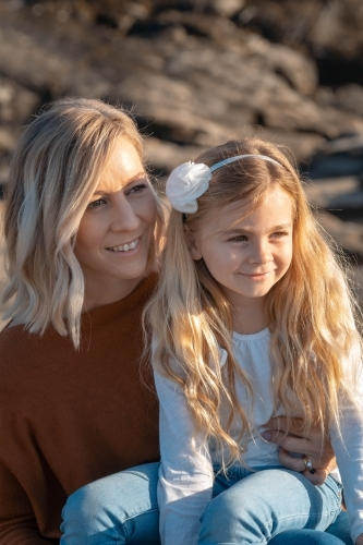 Young mother and daughter looking off camera at sunrise