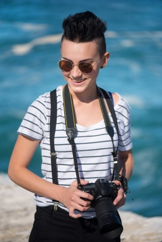 Young photographer with sunglasses smiling