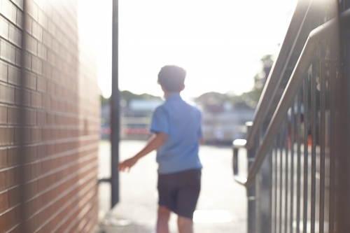Young school boy walking away from stairs at school playground