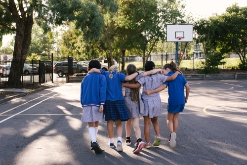 Young school girls walking together across a basketball court