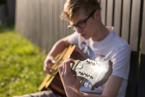 Young teen boy playing acoustic guitar by fence
