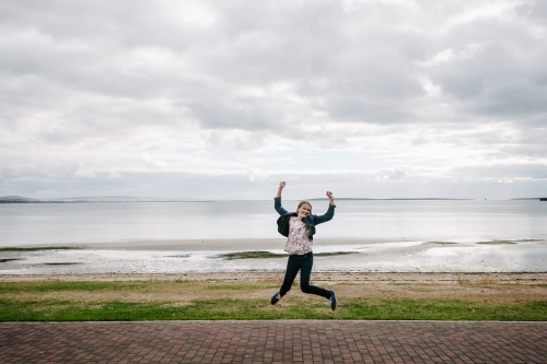 young teen girl jumping, ocean in the background