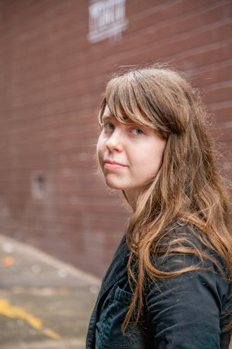 Young teen girl with a fringe in an alleyway looking sad