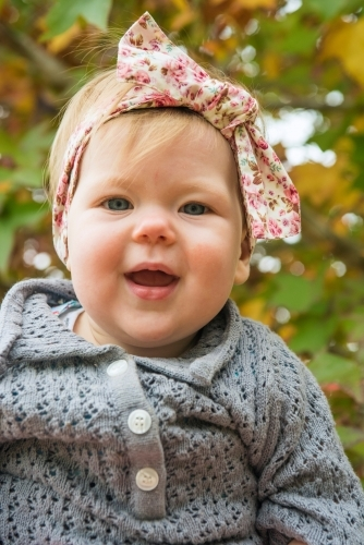 Young toddler looking at camera against background of autumn leaves
