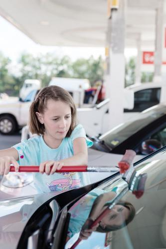 Young tween girl cleaning the windscreen of a car