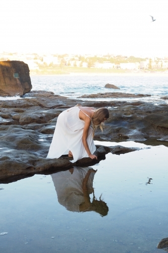 Young woman beside calm coastal rock pool