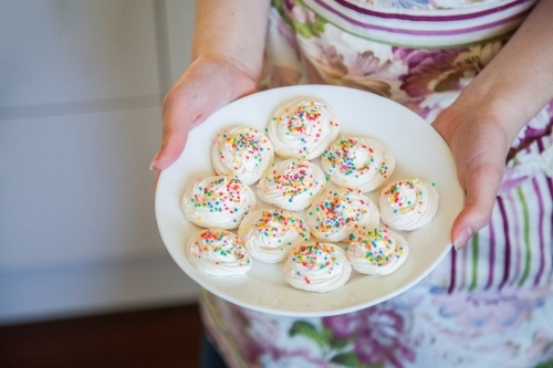 Young woman holding a plate of meringues with sprinkles