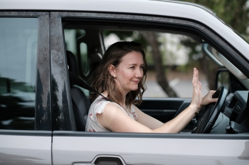 Young woman in 4wd vehicle thanking another driver by waving