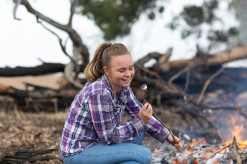 Young woman in checked shirt and jeans toasting marshmallows on campfire