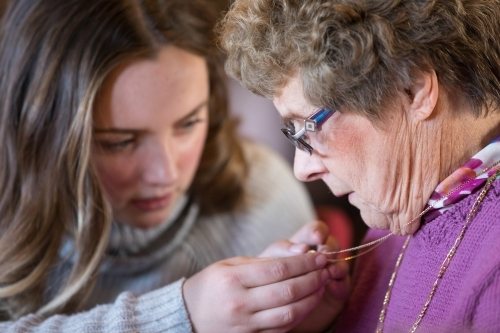 Young woman looking at older woman's locket